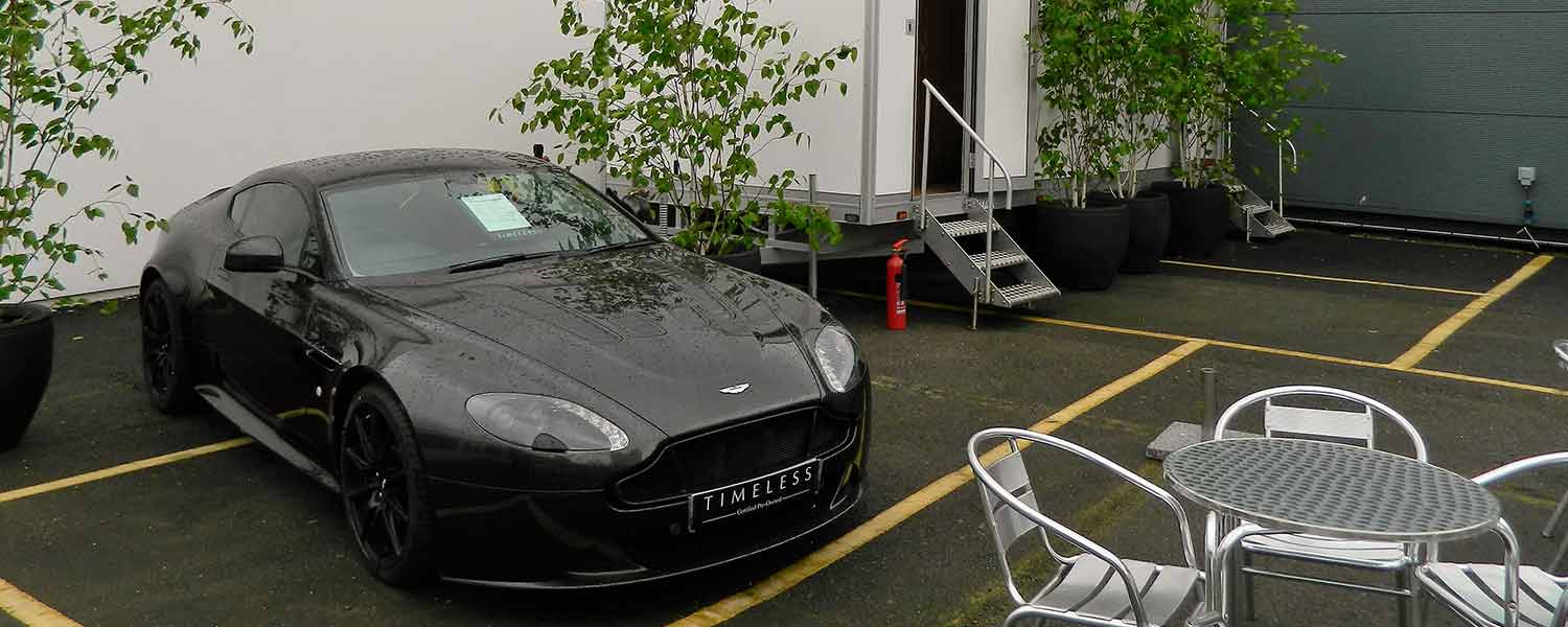 Any occasion toilet hire with black sports car outside